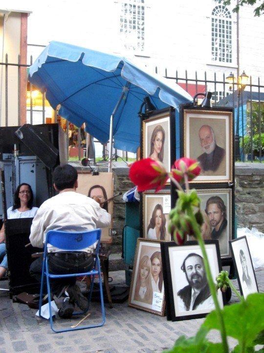 Portrait artist at work next to restaurant in historic old Quebec