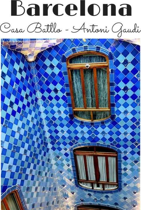 Blue tiles and wood framed windows at Casa Batllo courtyard in Barcelona