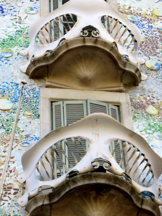 Casa Batllo mask like balcony railings and colorful mosaic facade - unique design by Catalan architect Antoni Gaudi