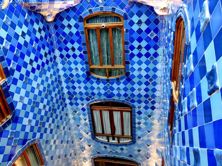 Casa Batllo upper courtyard dark tiles and smaller windows - designed by Catalan architect Antoni Gaudi between 1904 - 1906