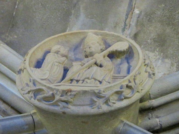 Stone carving of priest kneeling before St Augustine - Santa Anna Church - Barcelona Catalonia Spain