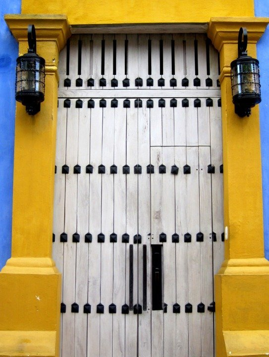 Black and white door with bright yellow frame in Cartagena Colombia