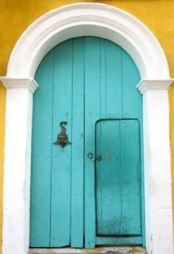 Colorful turquoise door on yellow building in Cartagena Colombia - colonial town on the Caribbean coast