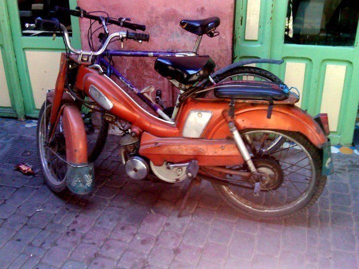 Scooters - a motorbike and a bicycle parked along the wall in the souks - Solo trip to Marrakech Morocco