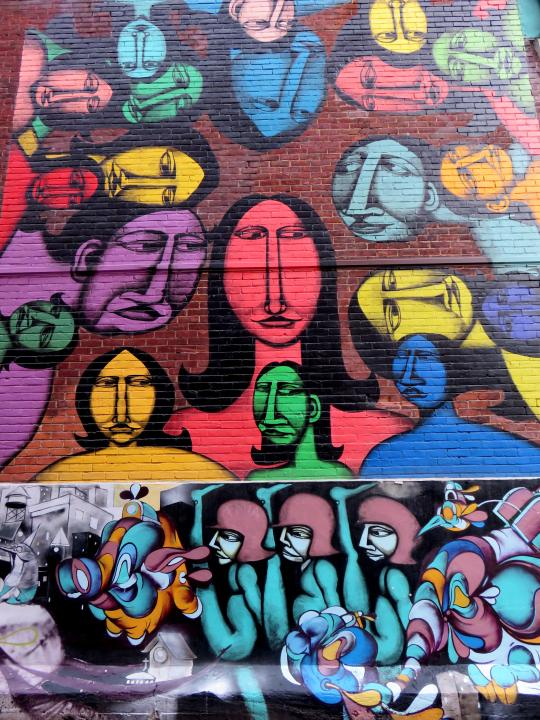 Colorful faces adorn a wall along St Denis Street - Montreal Quebec graffiti