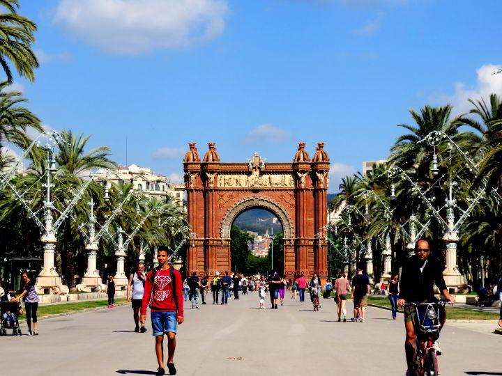 Walking along the Passeig de Lluis Companys promenade toward Arc de Triomf in Barcelona