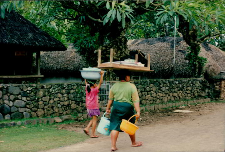 Woman balancing a table upon her head while walking along the road in Indonesia. A child accompanies her on her, carrying a set of bowls upon her head.