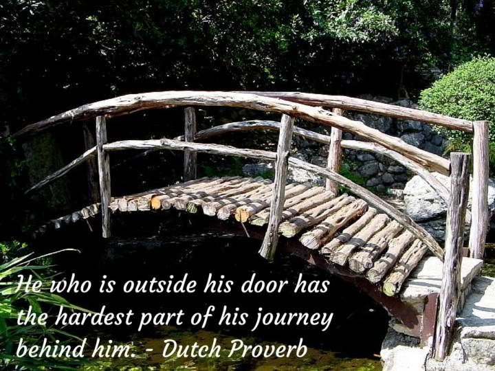 Wooden footbridge with inspirational travel quote: He who is outside his door has the hardest part of his journey behind him - Dutch proverb