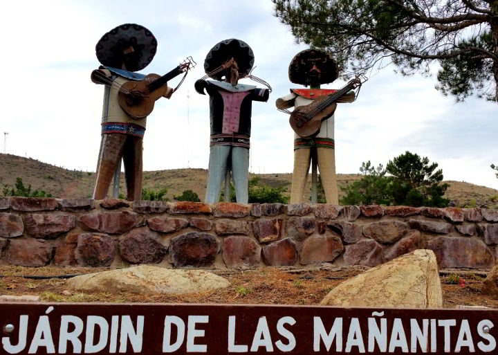 Three metal mariachis playing music in Baines Park - Alpine Texas - the words Jardin de las Mananitas are painted in white below the sculptures