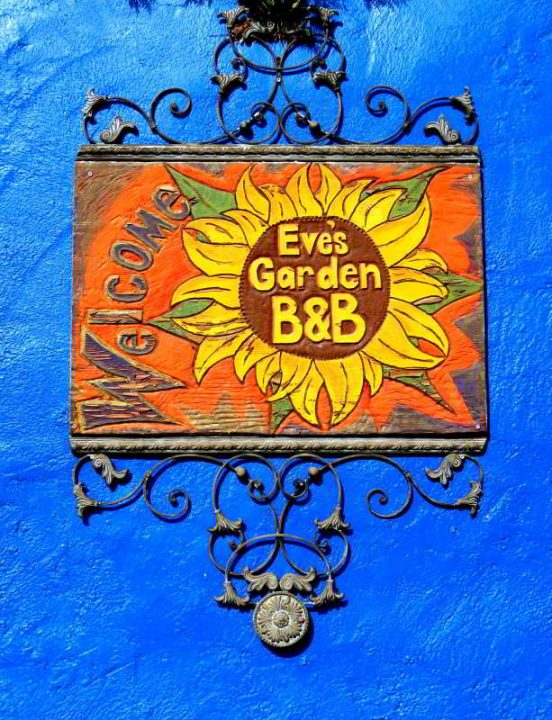 Eve's Garden Bed & Breakfast sign painted in orange, yellow, & green with a sunflower, on one of the bright blue walls of the papercrete structure in Marathon Texas