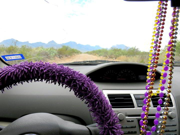 Toyota Yaris dashboard - purple steering wheel cover and colorful beads hanging from mirror