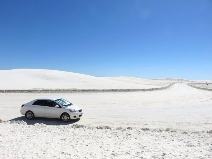 Toyota Yaris on white gypsum sand roadway at White Sands National Monument in NM