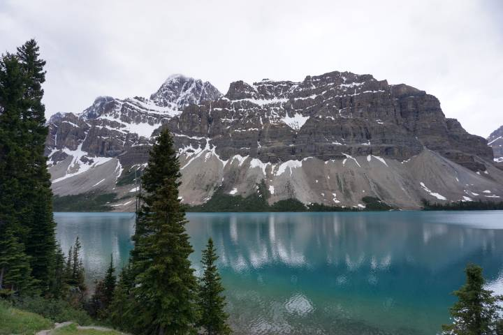 Bow Lake is glacier fed. Take a road trip on Icefields Parkway in Banff National Park Alberta Canada to see this stunning aquamarine color lake