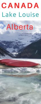 Red canoes at Lake Louise in spring time. Snow covered mountains and partially thawed lake waters - great Canadian road trip adventure