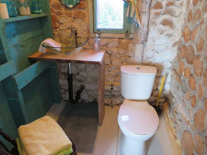 Basic bathroom with colorful turquoise shelves suits the basic needs - shower is located in a separate building