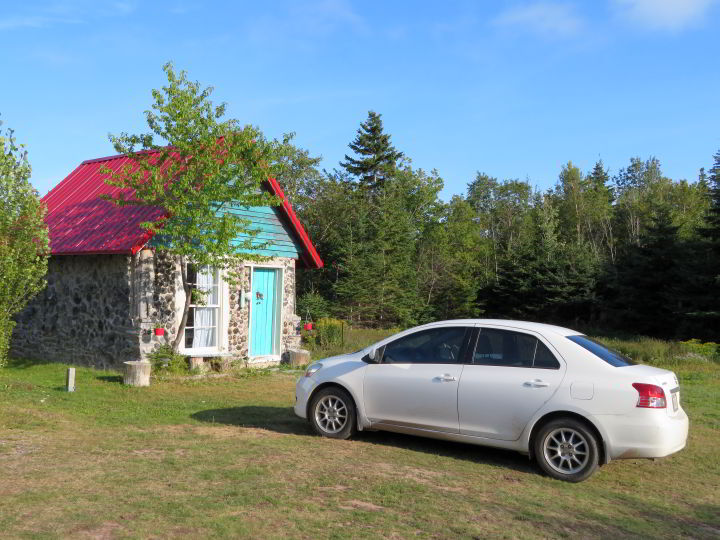 Tiny house painted turquoise with red rooftop is a cute cottage on the Cabot Trail near Cape Breton Highlands National Park