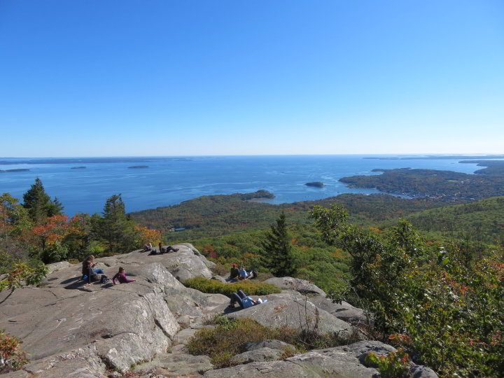 Hikers relax and enjoy the ocean view at Camden Hills State Park in mid-coast Maine
