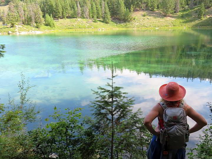 Female hiker looking at turquoise lake along Valley of the Five Lakes hike in Jasper AB