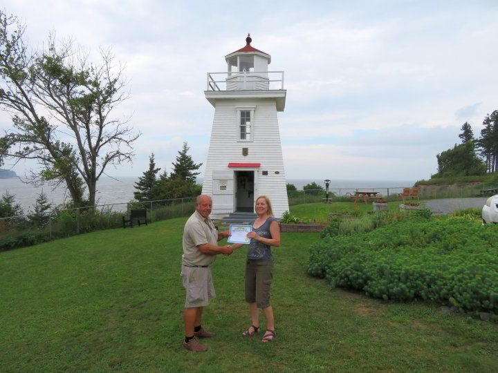 Lighthouse volunteer William Thompson presents Susan Moore with certificate