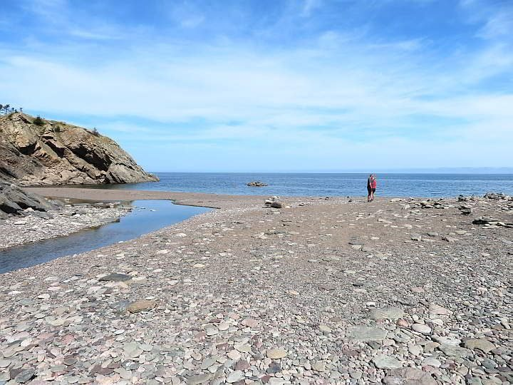 A couple stands on the beach at Meat Cove in Cape Breton Nova Scotia