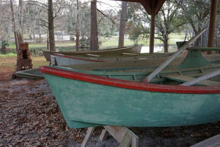 Turquoise and red dory boats at Vermilionville living history museum in Lafayette Louisiana