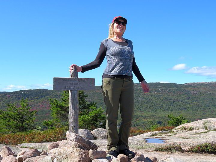 Solo hiker at the summit sign of Gorham Mountain Trail at Acadia National Park in Maine