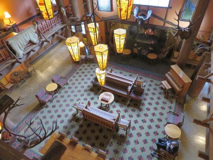 Overhead view of Lake McDonald Lodge lobby which features a huge fireplace and a piano