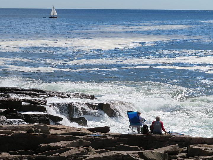 Two visitors at Acadia National Park sit upon the rocky shoreline watching waves and a sailboat