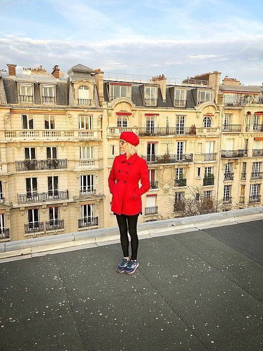 Wearing red jacket and beret, woman on Paris rooftop