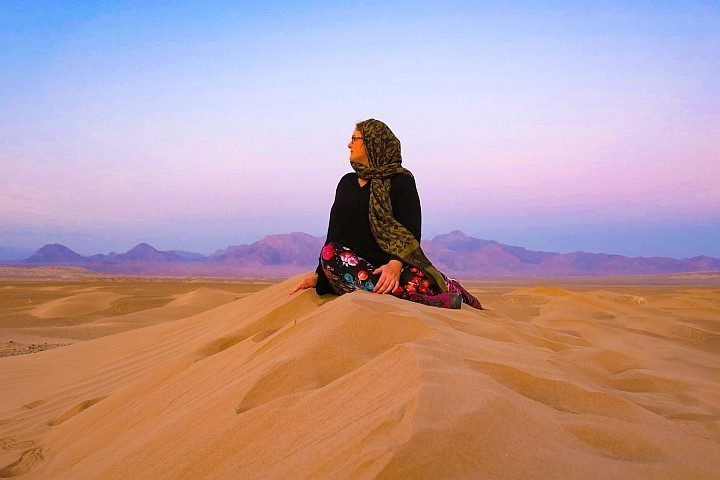 Solo traveler enjoying a beautiful sunset on the desert in Iran