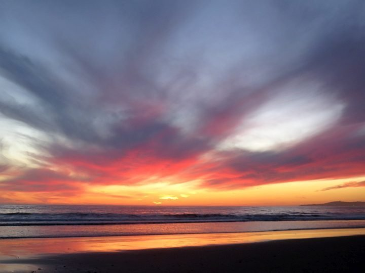 The sky bursts in brilliant hues of orange and yellow for this stunning beach sunset in Carpinteria