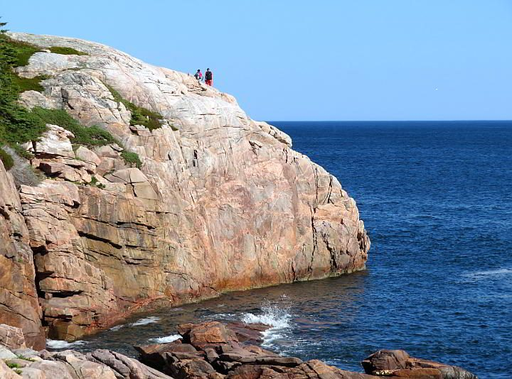Two hikers at an overlook on Jack Pine Trail along the famous Cabot Trail in Nova Scotia Canada