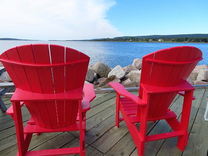 A couple of bright red Canada chairs at the waterfront in Annapolis Royal Nova Scotiava Scotia