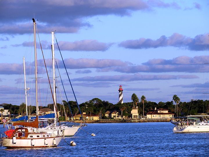Boats in the harbor with St Augustine Lighthouse in the background