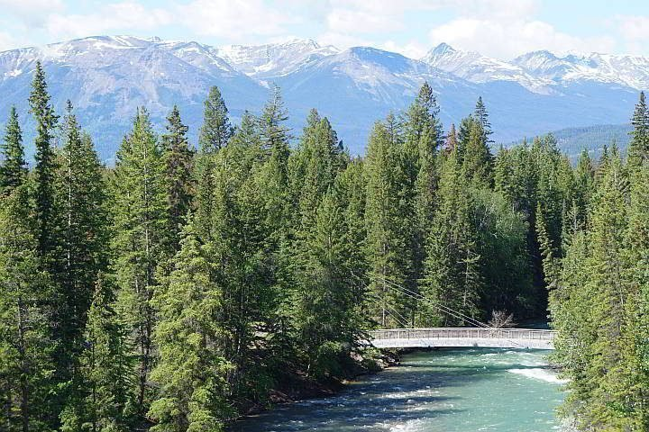 View of Maligne Canyon 5th bridge over Maligne River and mountain range in the background