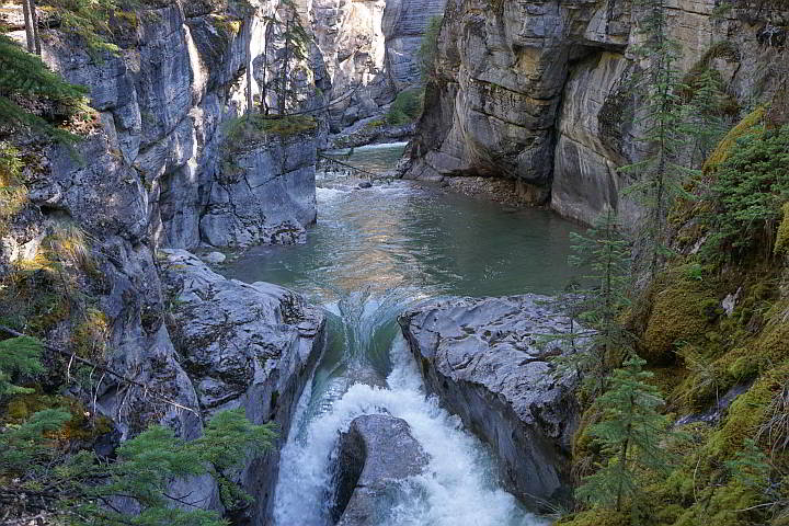 A small waterfall spills from a pool of water at Maligne River in Jasper National Park Canada