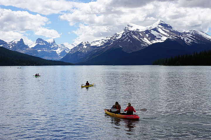 Rocky Mountains covered in snow offer panoramic views to kayakers at Maligne Lake Jasper Canada
