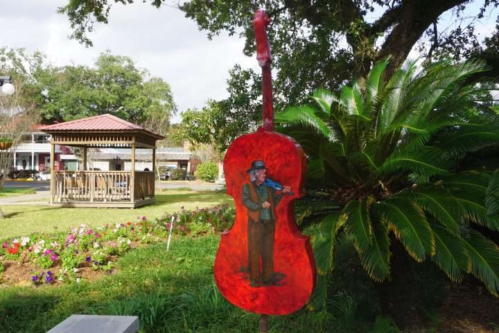 Large fiddle painted red with an image of a fiddle player on the back - part of Opelousas LA Fiddle Mania public art