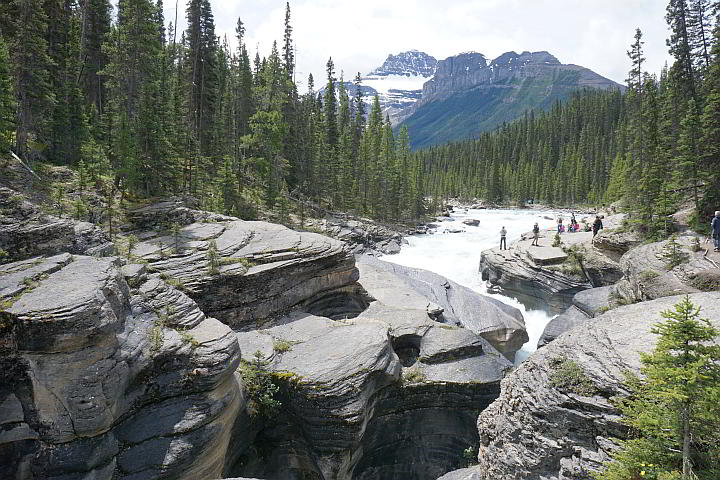 View of Mistaya Canyon Alberta with Rocky Mountains and tourists enjoying the falls