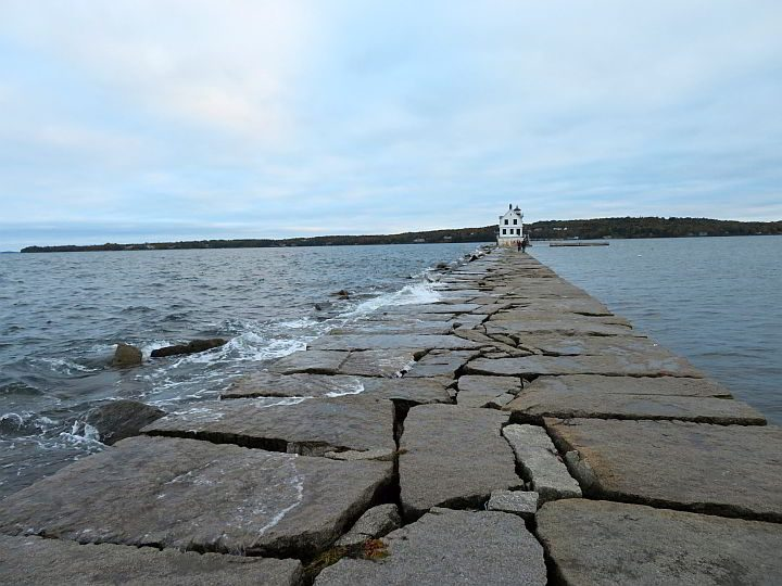 Waves wash over the Rockland Breakwater with the lighthouse in the distance