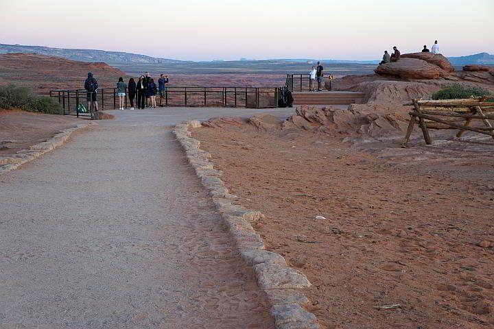 A dozen visitors at Horseshoe Bend Overlook at sunrise