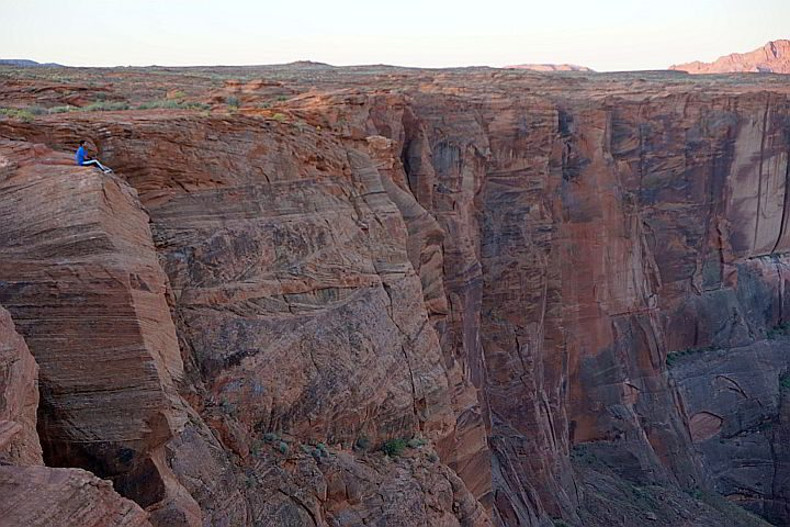 Risk taker sitting on the rock edge at Horseshoe Bend AZ