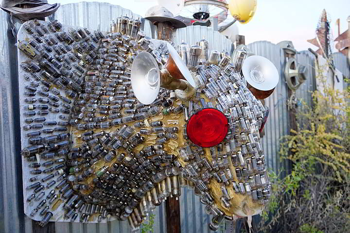 A sculpture of a cow's head made from discarded electronic parts