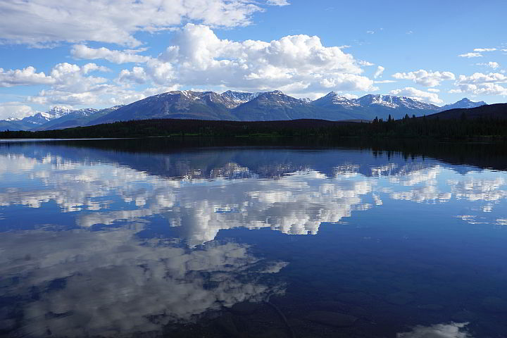 Puffy white clouds and Rocky Mountains reflection on Pyramid Lake Jasper AB