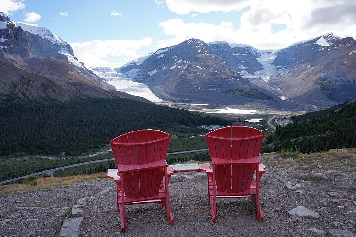Red chairs with view of the Rockies at Wilcox Pass trail